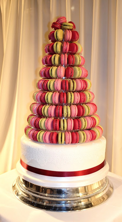 Dark pink, pink and green macarons on wedding cake.