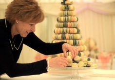 Preparing the macaron display for the wedding reception .