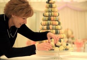 Preparing the macaron display for the wedding reception .