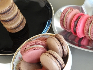 Pink and chocolate macarons on three plates